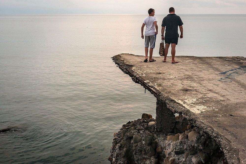 Two men are looking at the Black Sea, sitting on a concrete platform, Sukhumi, Abkhazia