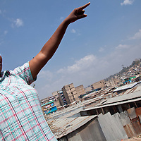 Beatrice gestures over the Mathare Valley as she shares information about her communtiy.