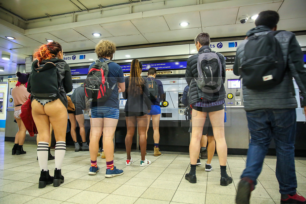 """© Licensed to London News Pictures. 13/01/2019. London, UK. Participants take part in 10th anniversary of 'No Trousers Tube Ride' by buying the travel tickets at Paddington London underground station. The """"No Pants Subway Ride"""" is an annual event staged by Improve Everywhere every January in New York City. The mission started as a small prank with seven guys and has grown into an international celebration of silliness, with dozens of cities including London around the world participating each year. Photo credit: Dinendra Haria/LNP"""