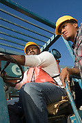 Construction worker sitting inside vehicle with another worker standing
