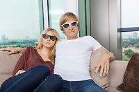 Relaxed couple wearing 3D glasses while sitting on sofa at home