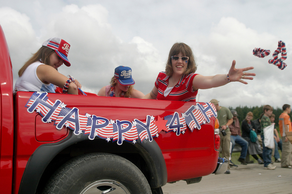 A happy rider clad in colorful costume tosses treats to people watching the fourth of July parade. The rider is in the back of bright red truck.