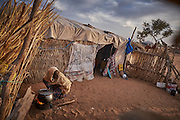 A woman cooks in a camp of displaced people in the neighbourhood of Chateau, Diffa, Niger on February 13, 2016. The camp is mixed between displaced people from Niger, Nigeria and Chad. They have fled attacks by the militant group Boko Haram on their villages and it's ongoing conflicts with the armies of each country. Caritas undertook a distribution of mosquito nets, cooking pots, sleeping covers, hygiene kits, clothes and cash transfers to the displaced. 228 households received support from Caritas among an estimated 1500 households in the  vicinity of Chateau. There is still great need. There is no school system in place for the children and the housing is not adequate for many as more people arrive each day escaping hostilities.