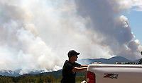 A man waits with his truck as the High Park Fire burned uncontrolled in the background west of Fort Collins, Colorado June 13, 2012.  The fire was estimated to be over 46,000 acres according to the county sheriff June 13, 2012. REUTERS/Rick Wilking  (UNITED STATES)