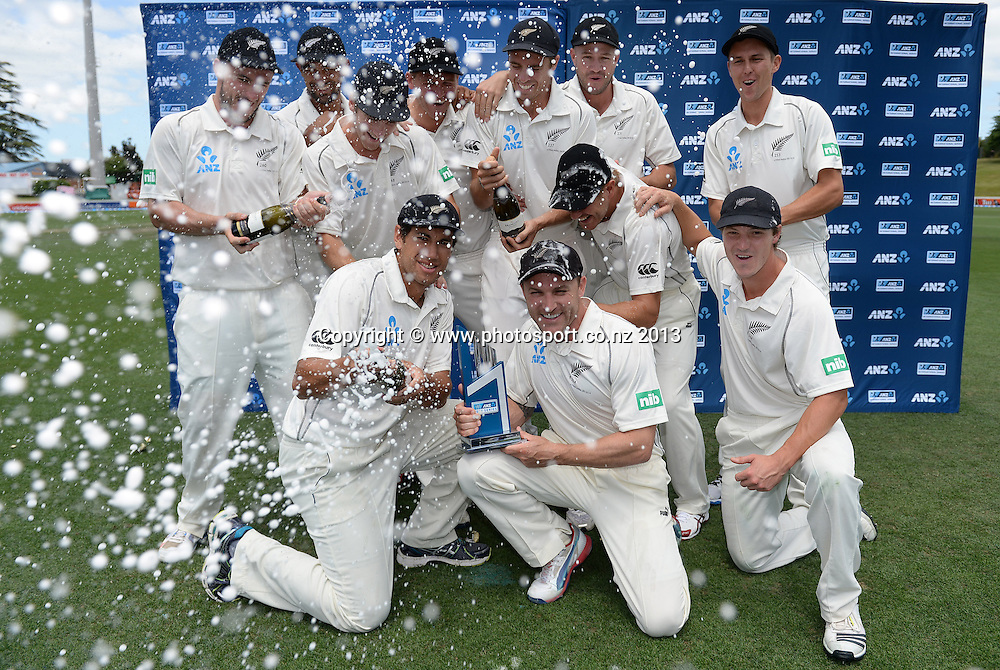 The New Zealand Cricket team celebrates as they pose for a team photo after a 2-0 series win over the West Indies on Day 4 of the 3rd cricket test match of the ANZ Test Series. New Zealand Black Caps v West Indies at Seddon Park in Hamilton. Sunday 22 December 2013. Photo: Andrew Cornaga / www.Photosport.co.nz