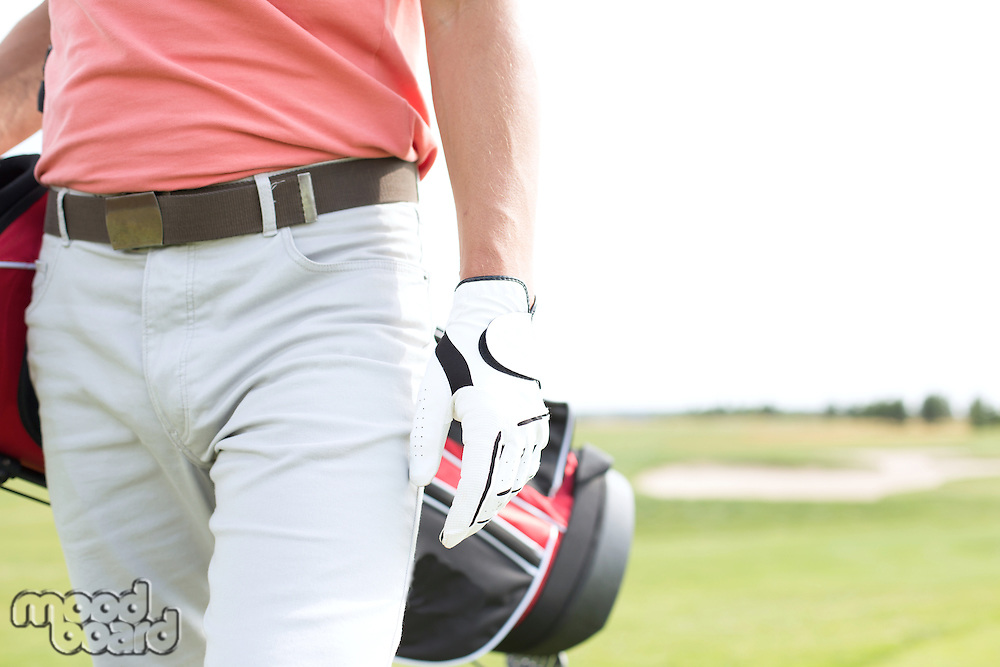 Midsection of man carrying golf club bag while walking at course