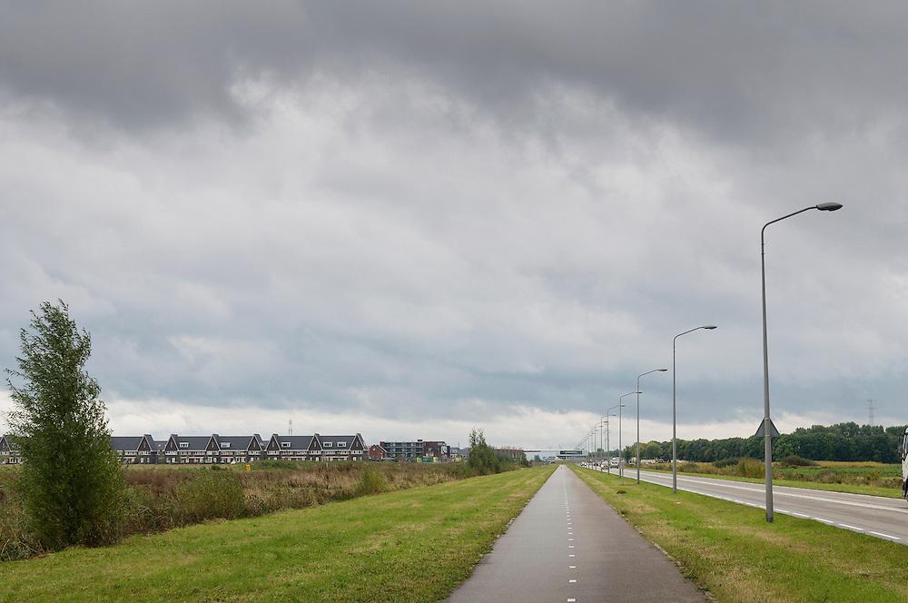 Nederland, Rosmalen, 20121013..Kaarsrechte weg langs de nieuwbouwwijk..Bij Rosmalen, gemeente Den Bosch wordt een nieuwe stad gebouwd, De Groote Wielen. In de nieuwe wijk worden 6500 woningen gebouwd. Het landschap verandert van een polderlandschap met agrarische bestemming in een stadslandschap..De rafelranden van een nieuwe stad...Netherlands, Rosmalen, 20121013..Candle Straight road along the new district..Near Rosmalen a new town is being build,  De Groote Wielen. In the new district 6,500 homes are built. The landscape changes from a polder landscape with agricultural destination in a city landscape..The fringes of a new city.