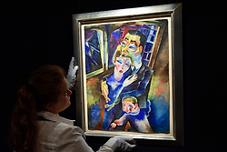 "© Licensed to London News Pictures. 15/06/2017. London, UK. A staff member hangs ""Self-Portrait with my wife Londa and my son Titus"", 1923, by Conrad Felixmüller (estimate GBP300-500k). Preview of Impressionist and Modern art sale, which will take place at Sotheby's New Bond Street on 21 June.  Photo credit : Stephen Chung/LNP"