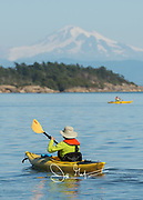 People paddle kayaks near Sucia island, a Washington state park, with Mount Baker seen in the background.