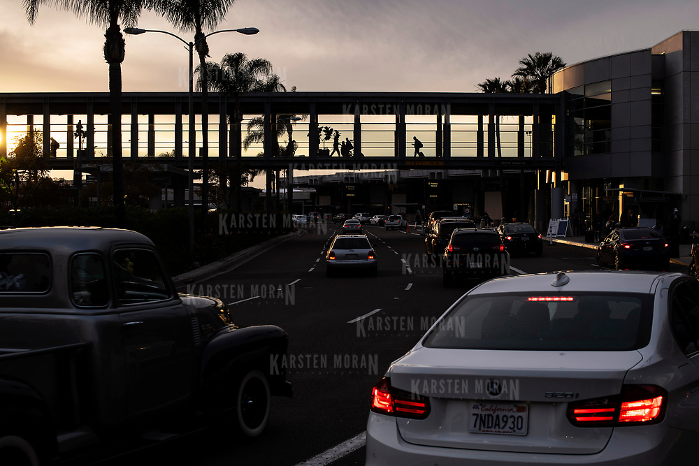 March 18, 2018 - San Diego, Calif. : Vehicles and pedestrians arrive at and depart from San Diego airport at sunset. Am antique automobile can be seen in the foreground. CREDIT: Karsten Moran