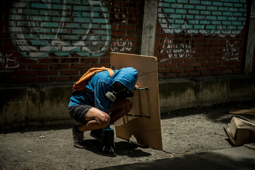 CARACAS, VENEZUELA - JUNE 3, 2017:  An anti-government protester takes cover behind a homemade shield, as security forces fire tear gas, rubber bullets and buckshot into the crowd of protesters. The streets of Caracas and other cities across Venezuela have been filled with tens of thousands of demonstrators for nearly 100 days of massive protests, held since April 1st. Protesters are enraged at the government for becoming an increasingly repressive, authoritarian regime that has delayed elections, used armed government loyalist to threaten dissidents, called for the Constitution to be re-written to favor them, jailed and tortured protesters and members of the political opposition, and whose corruption and failed economic policy has caused the current economic crisis that has led to widespread food and medicine shortages across the country.  Independent local media report nearly 100 people have been killed during protests and protest-related riots and looting.  The government currently only officially reports 75 deaths.  Over 2,000 people have been injured, and over 3,000 protesters have been detained by authorities.  PHOTO: Meridith Kohut