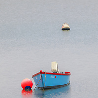 Massachusetts South Shore harbor scenery of a blue dinghy on a rainy day in May.  <br />