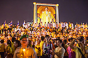 05 DECEMBER 2012 - BANGKOK, THAILAND: Thai government officials and business leaders participate in a candle light vigil for the King during the public ceremony to celebrate the birthday of Bhumibol Adulyadej, the King of Thailand, on Sanam Luang, a vast public space in front of the Grand Palace in Bangkok Wednesday night. The King celebrated his 85th birthday Wednesday and hundreds of thousands of Thais attended the day long celebration around the Grand Palace and the Royal Plaza, north of the Palace. The Thai monarch is revered by most Thais as unifying force in Thailand's society, which is not yet recovered from the political violence of 2010.      PHOTO BY JACK KURTZ
