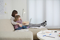 Mother and daughter with laptop in living room