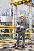 Full length of young businessman with building plans outside industry