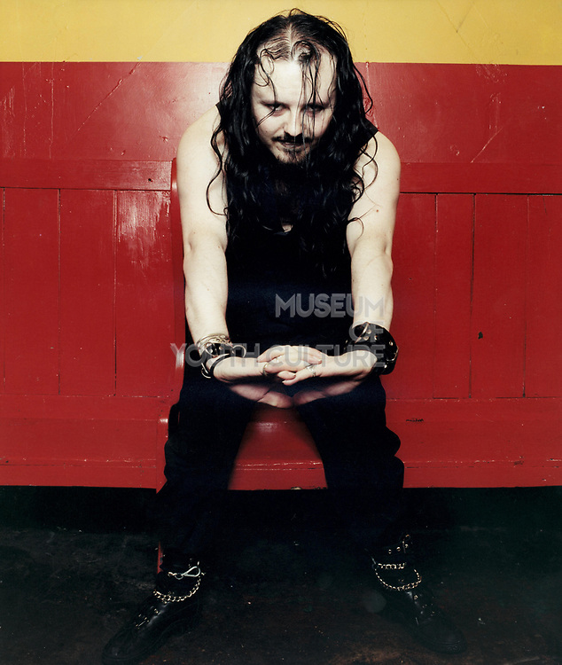 Goth man posing with arms stretching standing against a red and yellow wall.