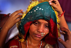 Sarita, 15-years-old, is seen covered in tears and sweat before she is sent to her new home with her new groom. The previous day, she and her eight-year-old sister Maya were married to another set of siblings  on the Hindu holy day of Akshaya Tritiya, or Akha Teej, in Rajasthan, India on April 29, 2009.