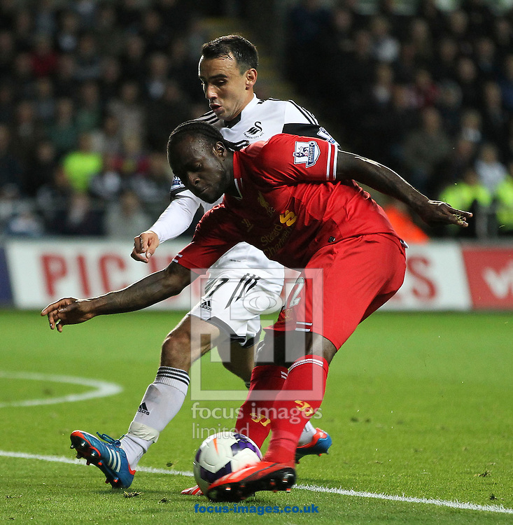 Picture by Mike  Griffiths/Focus Images Ltd +44 7766 223933<br /> 16/09/2013<br /> Leon Britton of Swansea City and Victor Moses of Liverpool during the Barclays Premier League match at the Liberty Stadium, Swansea.