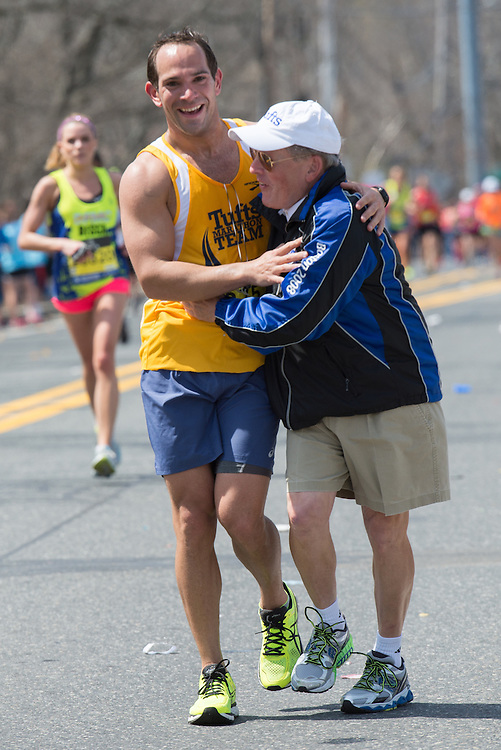 4/18/16 – Natick, MA – Tufts Marathon Team runner Kyle Backstrom and Tufts Marathon Team coach Donald Megerle embrace at Mile 9 of the 2016 Boston Marathon in Natick, MA on April. 18, 2016. (Sofie Hecht / The Tufts Daily)