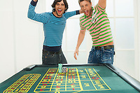 Two young men celebrating on roulette table portrait