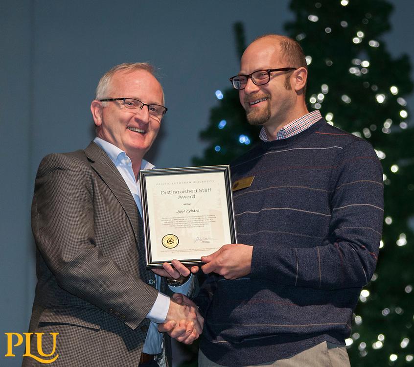 Allan Belton present an award to Joel Zylstra at the PLU Christmas Brunch, Thursday, Dec. 14, 2017. (Photo: John Froschauer/PLU)