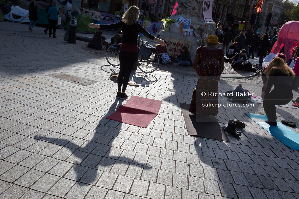 Environmental activists practice yoga while protesting about Climate Change during an occupation of Trafalgar Square in central London, the third day of a two-week prolonged worldwide protest by members of Extinction Rebellion, on 9th October 2019, in London, England.