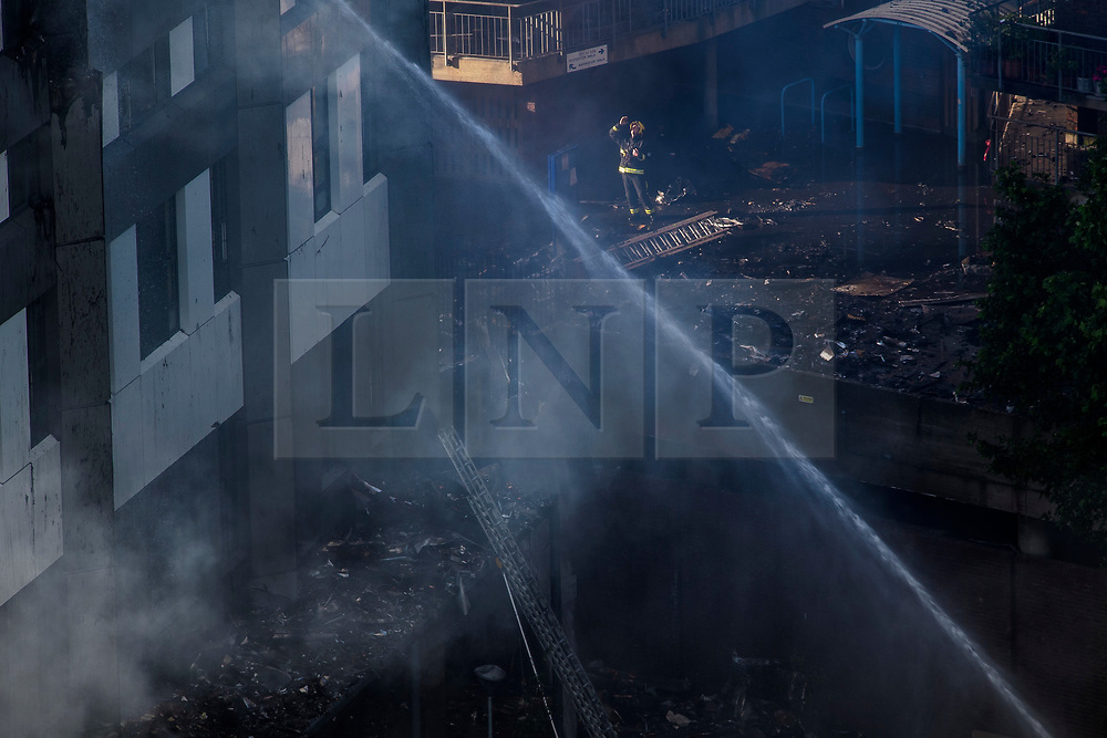 © Licensed to London News Pictures. 14/06/2017. London, UK. A firefighter looks on at the scene of a huge fire at the Grenfell tower block in west London. The blaze engulfed the 27-storey building with hundreds of firefighters attending the scene. There are reports of people trapped in the building and multiple fatalities. Photo credit: Ben Cawthra/LNP