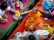 05 JANUARY 2019 - MINBURI, BANGKOK, THAILAND:  Buddhist monks collect alms from people along Khlong Saen Saeb, at the Kwan Riam Floating Market in Minburi, east of downtown Bangkok. People gather on both sides of the khlong (canal) between Wat Bamphen Nuea and Wat Bamphen Tai and monks in boats go past them as people present the monks with food, flowers, and other offerings. It is the only place in Bangkok where monks regularly use boats for their alms rounds.       PHOTO BY JACK KURTZ