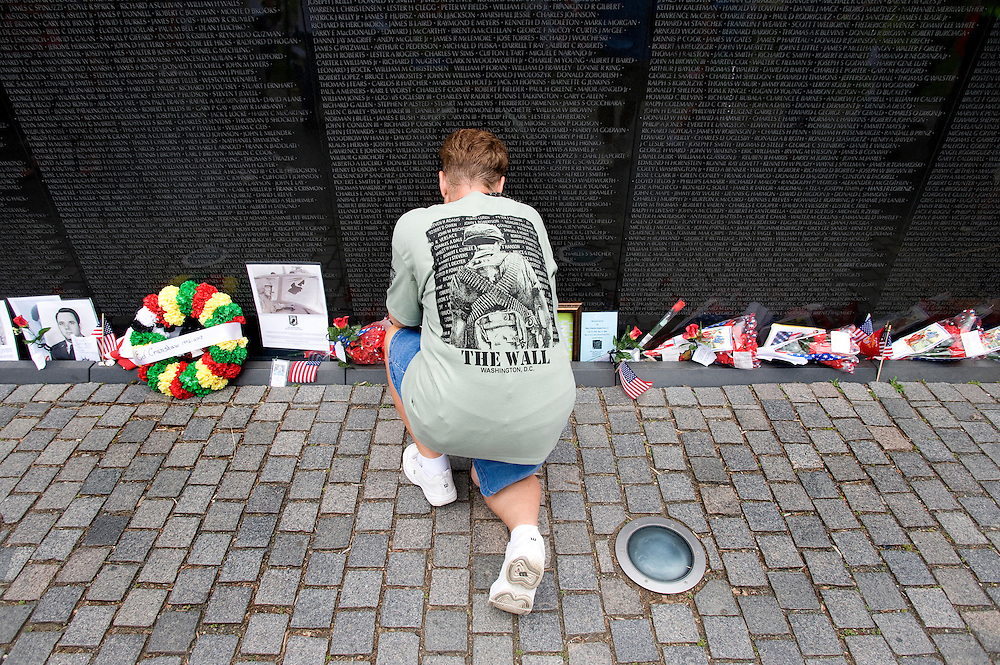A visitor to the Vietnam Veterans Memorial examines some of the memorabilia left at the monument during a visit on Sunday May 24, 2009.