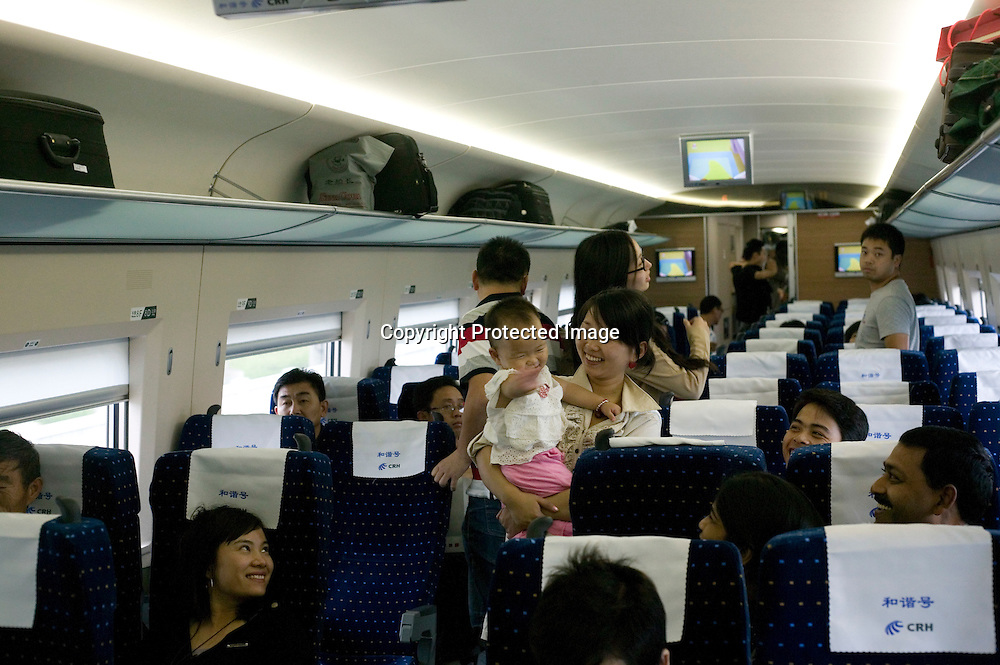 Beijing, September 11 , 2011 : passengers looks on as a woman hlds a crying baby. the passenger-dedicated trunk line opened in June 2011, reducing the 1,318 km journey between Beijing and Shanghai to less than 5 hours. Trains reach top speeds of 300 km/h (186 mph) for the entire trip.