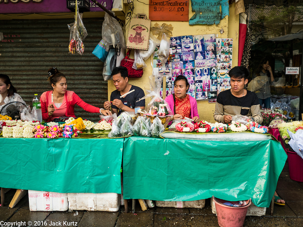 24 FEBRUARY 2016 - BANGKOK, THAILAND:  People make flower garlands in a sidewalk stall in front of Pak Khlong Talat in Bangkok. Bangkok government officials announced this week that vendors in Pak Khlong Talat, Bangkok's well known flower market, don't have to move out on February 28. City officials are trying to clear Bangkok's congested sidewalks and they've cracked down on sidewalk vendors. Several popular sidewalk markets have been closed in recent months and the sidewalk vendors at the flower market had been told they would be evicted at the end of the month but after meeting with vendors and other stake holders city officials relented and said vendors could remain but under stricter guidelines regarding sales hours. The flower market is one of the best known markets in Bangkok and has become a popular tourist destination.       PHOTO BY JACK KURTZ