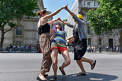 """© Licensed to London News Pictures. 21/06/2017. London, UK. A woman wears a hard hat with the text """"No DUP"""" as Anti-Tory protesters stage a """"dance off"""" outside Downing Street following the Queen's Speech in Parliament. Photo credit : Stephen Chung/LNP"""