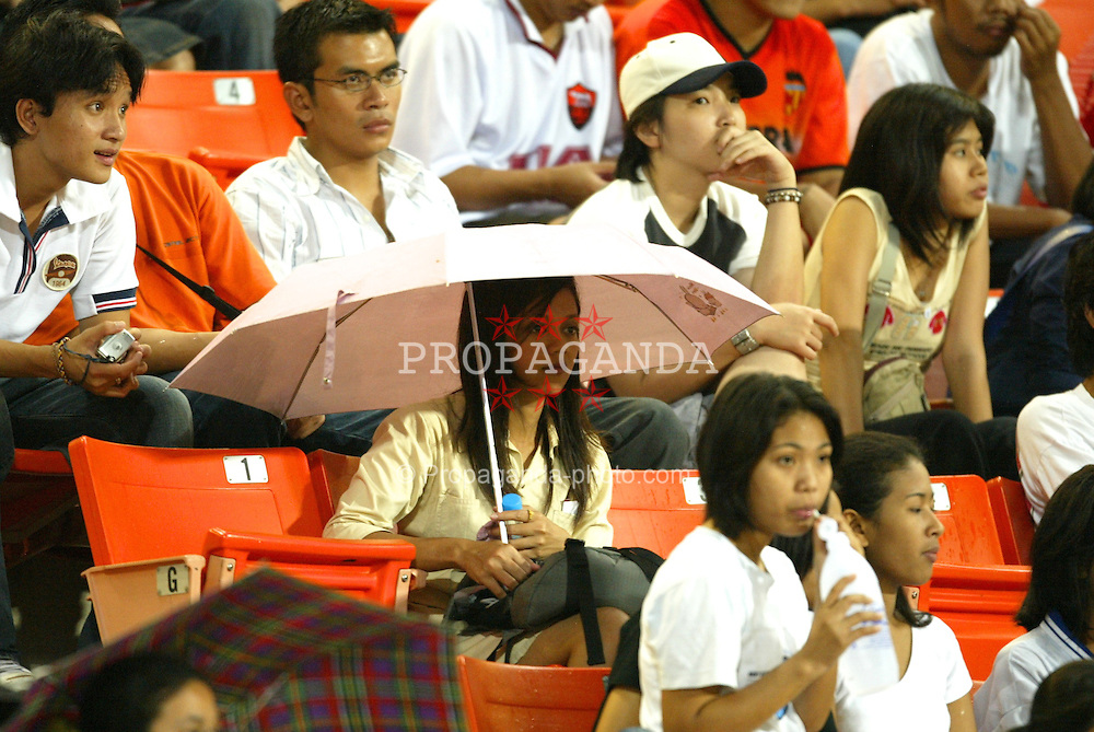 BANGKOK, THAILAND - Wednesday, July 23, 2003: A Thai Liverpool fan tries to keep dry during a training session in at the Rajamangala National Stadium. (Pic by David Rawcliffe/Propaganda)