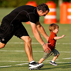 August 6, 2011; Metairie, LA, USA; New Orleans Saints quarterback Drew Brees plays with his son Baylen Brees on the practice field following a training camp practice at the New Orleans Saints practice facility. Mandatory Credit: Derick E. Hingle