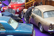 UNITED KINGDOM, London: 24 April 2018 A visitor makes his way through a collection of classic cars inside The Royal Horticultural Halls, Westminster. The cars form part of the Spring Classics: An Important Auction of Fine Historic Automobiles at The Royal Horticultural Halls, Westminster. The auction will see a collection of privately owned cars be auctioned this evening April 24th 2018. Rick Findler  / Story Picture Agency