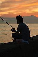 Japanese Fisherman at Sunset at Shonan Beach, content to just sit in the twilight with his pole in hopes of catching a fish.