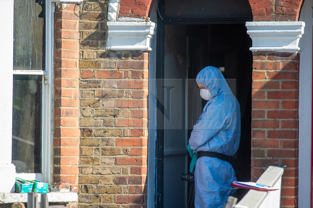 © Licensed to London News Pictures. 25/04/2020. London, UK. A forensic investigator wearing a protective suit and facemask stands in the doorway of a property at the scene of a fatal house fire. A man has died in a house fire in Earlsfield, Wandsworth. Firefighters found the man in a ground floor bedroom. He was brought out of the property by fire crews but he died at the scene. London Fire Brigade was called at 07:36 BST and the fire was under control by 08:33 BST. Photo credit: Peter Manning/LNP