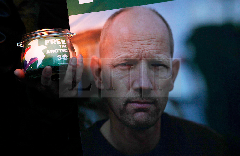 Licensed to London News Pictures 18/10/2013<br /> London.UK. <br /> An activist holds a candle and a photograph of one of the Artic 30 Greenpeace activists, detained in a Russian jail, during a vigil outside the Russian embassy in London. <br /> Photo credit: Anna Branthwaite