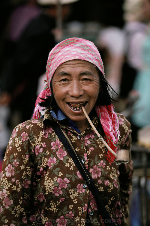 Woman smokes a pipe at the Menghan Sunday market, Xishaungbanna, China.