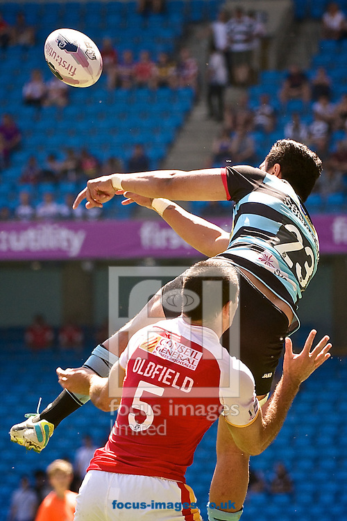 Denny Solomona of London Broncos pads the ball under pressure from Michael Oldfield of Catalans Dragons during the First Utility Super League match at the Etihad Stadium, Manchester<br /> Picture by Ian Wadkins/Focus Images Ltd +44 7877 568959<br /> 17/05/2014