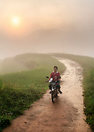 A Vietnamese man rides a motorbike on a track of Thong Nguyen valley, Hoang Su Phi, Vietnam, Southeast Asia