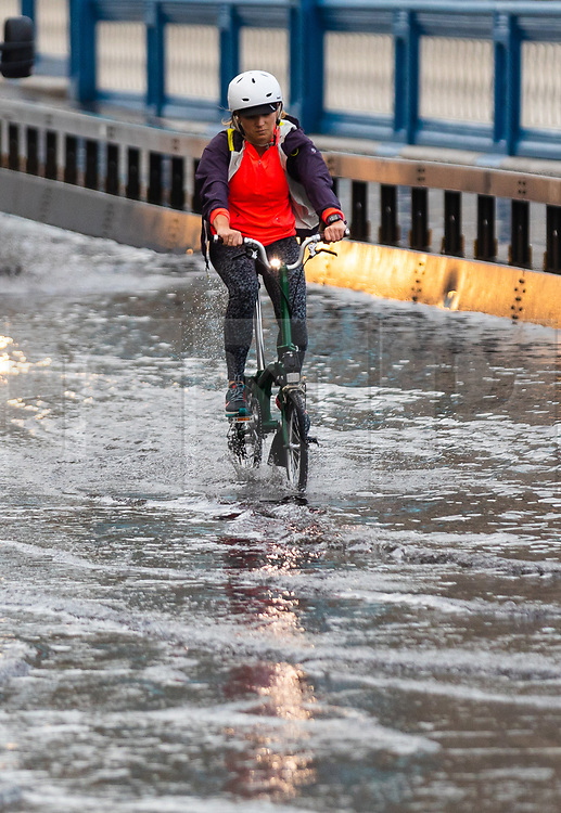 © Licensed to London News Pictures. 06/10/2019. London, UK. A cyclist rides through flooding and excess surface water on Tower Bridge this morning following heavy rain and wet weather in the capital last night. Weather forecasts predict that most of the UK will be experience heavy rain and storms during the next few days. Photo credit: Vickie Flores/LNP