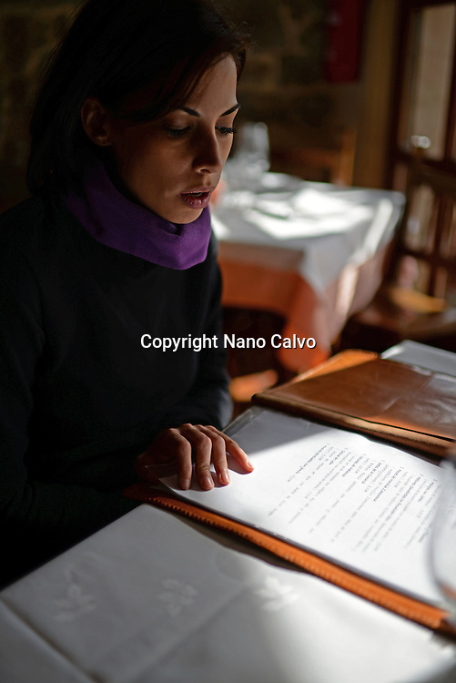 Young woman reading restaurant menu