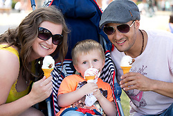 © Licensed to London News Pictures. 24/07/2013. Stratford upon Avon, Warwickshire, UK. As temperatures rise after the recent thunderstorms and rain, people flocked to Stratford upon Avon to start enjoying the sun. Pictured, two years old Tanner McNally, mum Jo and dad Ezra enjoy an ice cream near the river. Photo credit : Dave Warren/LNP