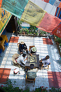 A group of men play a game of Chinese Mah Jongg under a few strings of Tibetan prayer flags in Dequin, China (Tibet).