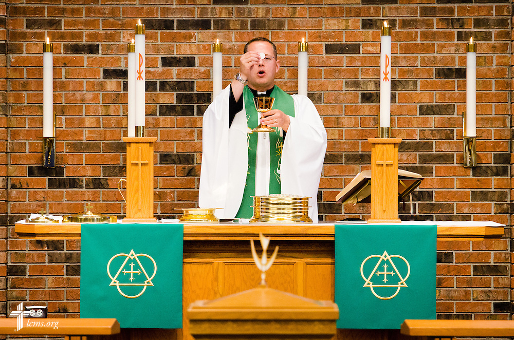 The Rev. Jonathan Huehn, associate pastor, prepares the Sacrament Sunday, July 27, 2014, during worship at Christ Lutheran Church in Normal, Ill. LCMS Communications/Erik M. Lunsford