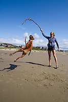 Image of young woman playing with dog in Manzanita, Oregon.