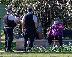 © Licensed to London News Pictures. 05/04/2020. London, UK. Police question a man sitting in Normand Park Fulham. Members of the public come out to exercise in Normand Park as temperatures reach over 21c this weekend. The Government has urged the public not to leave home during the fine weather to help save lives as the Coronavirus crisis continues. Photo credit: Alex Lentati/LNP