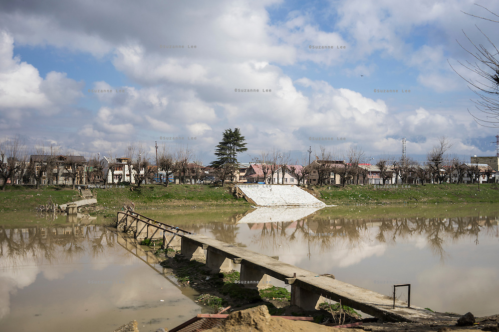 A sand bank is built on the banks of the river as a broken bridge is seen in Srinagar, the capital of Jammu and Kashmir, India, on 25th March 2015. Nearly 2500 villagers including Srinagar, the capital of the state of Jammu and Kashmir, was devastated by severe floods and landslides in September 2014 the worst in 60 years, displacing millions of people, many of them children. Photo by Suzanne Lee for Save the Children