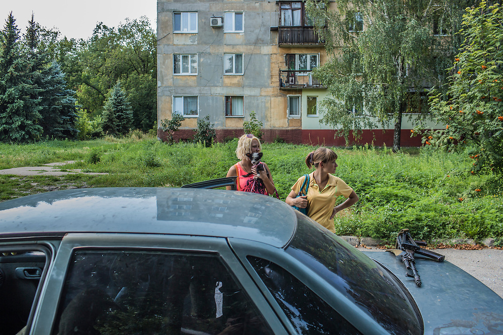 Residents of the Ploshchadka neighborhood, which has been heavily bombarded in recent days, await an escort from pro-Russia rebels to leave the neighborhood on Wednesday, July 30, 2014 in Donetsk, Ukraine.